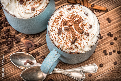 Poster Hot chocolate with whipped cream in mug on a wooden table.