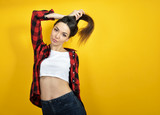 Hipster girl in jeans, checked shirt and hat posing over yellow