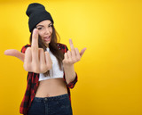 Hipster girl in jeans, checked shirt and hat showing middle fing