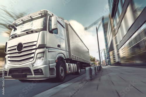 silver truck driving in the city