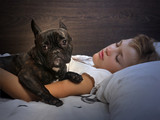 Young girl sleeping on the bed. Dog - French Bulldog. Evening or night, in a dark room
