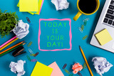 Today is your day. Office table desk with supplies, white blank note pad, cup, pen, pc, crumpled paper, flower on blue background. Top view