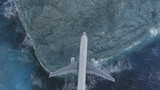 Passenger aircraft flying over the sea and the mountain at rain time