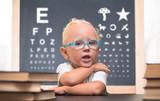 Ребенок в очках сидит за столом на фоне таблицы для проверки зрения