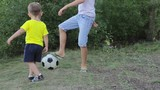 Two brothers playing with soccer ball in the park