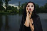 Beautiful brunette woman in black dress and black cloak