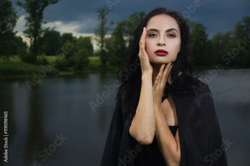 Poster Beautiful brunette woman in black dress and black cloak