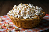 salted popcorn in a wicker basket on a napkin