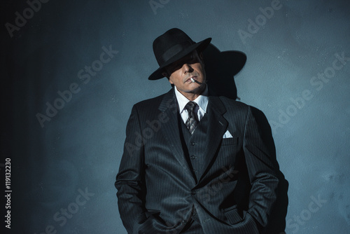 Retro 1940 film noir gangster wearing suit and hat. Smoking ciga