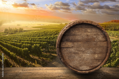 Panel Szklany Red wine with barrel on vineyard in green Tuscany, Italy