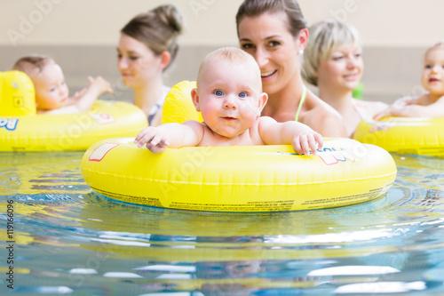 Leinwandbild Motiv Mamas und ihre Babys haben Spaß mit Spielzeug beim Säuglingsschwimmen