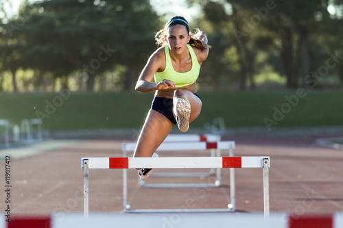 Póster Young athlete jumping over a hurdle during training on race trac
