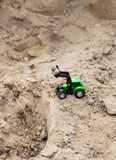 childrens toy tractor on a green field