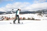 Young woman on snowboard in winter