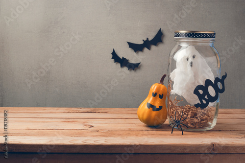 Poster Halloween holiday decoration with ghost in jar and pumpkin with scary face on wo