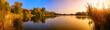 Leinwanddruck Bild - Sonnenuntergang an einem See, ein Panorama in Gold und Blau