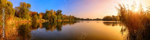 Leinwanddruck Bild Sonnenuntergang an einem See, ein Panorama in Gold und Blau
