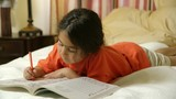 A sweet little Hispanic girl lying on a bed colors contentedly in her coloring book.