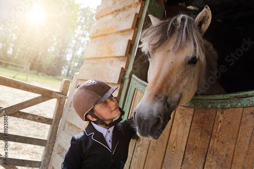 Poster jeune fille 11 ans en tenue d'équitation dans écurie, box avec cheval