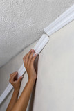 Fototapety Installing crown molding on ceiling in room with painted wall. Fragment of molding, horizontal view.