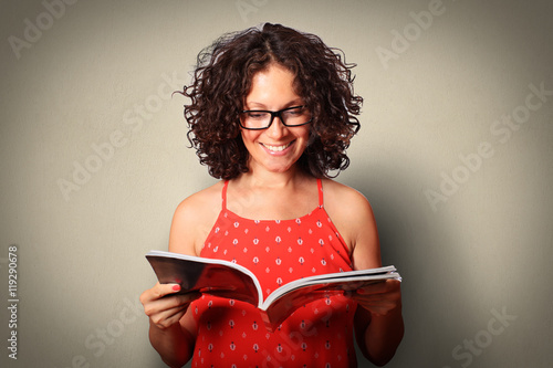 Young woman in red dress reads and smiles Poster