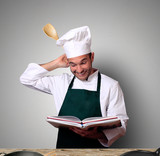 Chef in the kitchen with recipe book - 119291419