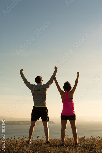 Sporty runner couple rising arms in victory sign after successful training outdoor on the coast facing the sun showing back Poster