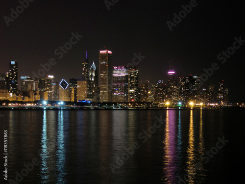 Chicago skyline at night across water with reflections