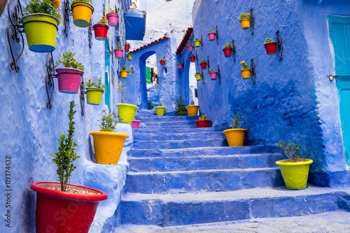 Foto op Plexiglas Marokko Morocco, Chefchaouen or Chaouen is most noted for its small narrow streets and neighborhoods painted in variety of vivid blue colors. Plantings in colorful pots line the narrow corridors.