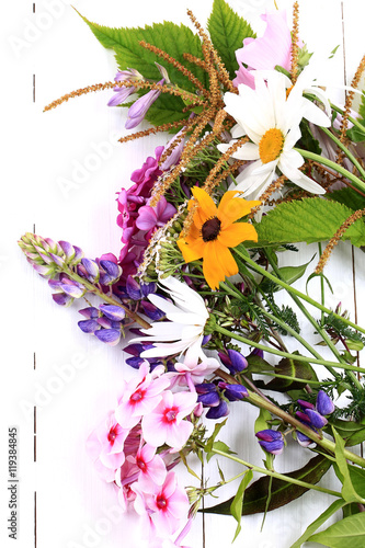 garden flowers on white wooden background view from above a flat appearance