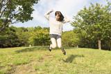 若い女性 公園 ジャンプ 笑顔 全身