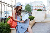Cheerful young woman sitting and reading book in the city