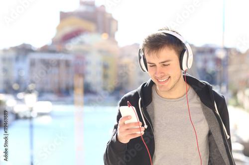 Fotobehang Muziek Teenager walking listening music from smart phone