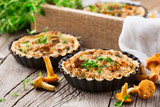 Homemade tarts of puff pastry with seasonal chanterelle mushrooms, cheese, thyme and onion on rustic wooden table