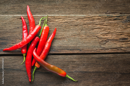 Poster red chili peppers on dark wooden background