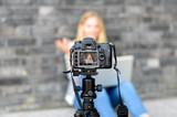 Young woman on camera LCD screen waving - 119610267