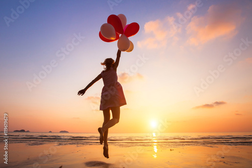 imagination, happy girl jumping with multicolored balloons at sunset on the beac Poster