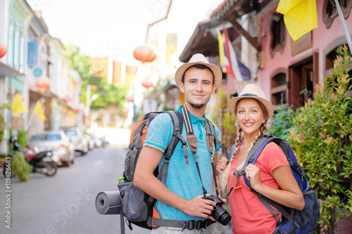 Foto Murales Travel and tourism. Couple of backpackers walking together on asian street.
