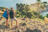 Traveling and trekking concept. Young loving couple walking on mountains near the sea.