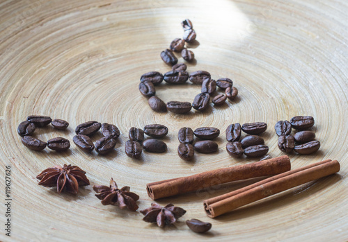 Fotobehang Koffiebonen Coffee beans on a table made of bamboo, with cinnamon and star anise.