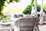 Porch with white wicker chairs and table - 119633266