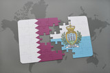 puzzle with the national flag of qatar and san marino on a world map background.