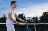 Tennis player standing by the net and holding racket