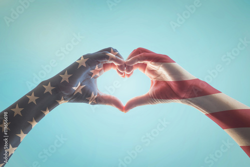 American flag red white blue star pattern on people hands in heart love shape is Poster