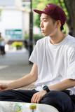 足元のスケートボードと休憩する男性