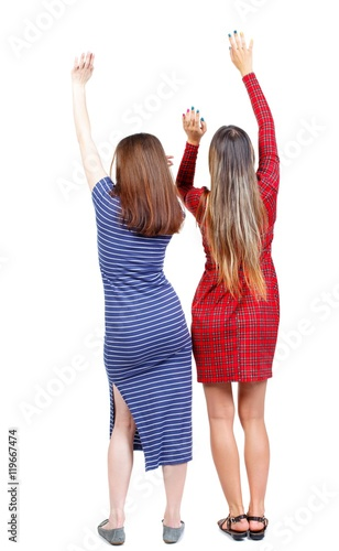 Back view of two dancing young women. . backside view of person. Rear view people collection. Isolated over white background. Two girls in dresses dancing hands up. - 119667474