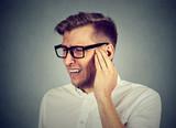 Tinnitus. Sick man having ear pain touching painful head