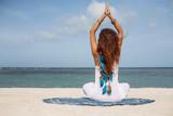 Fototapety Morning meditation. Young beautiful woman doing yoga on beach