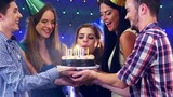 Girl with friends men celebrate birthday and blow out candles on cake. Happy birthday celebrate at nightclub. 4k