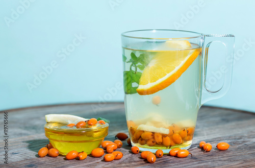 Poster Transparent cup of tea with sea buckthorn, honey and lemon